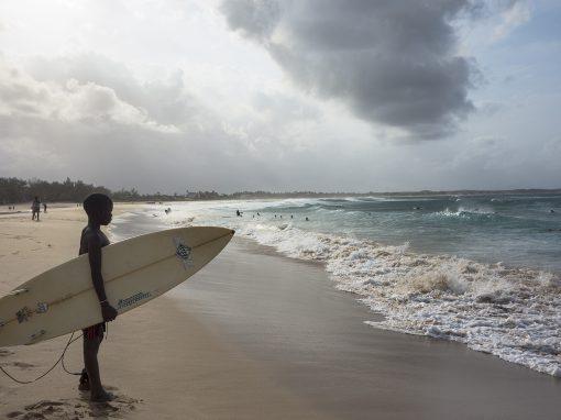 Pojken står vid strandkanten med surfbräda under armen
