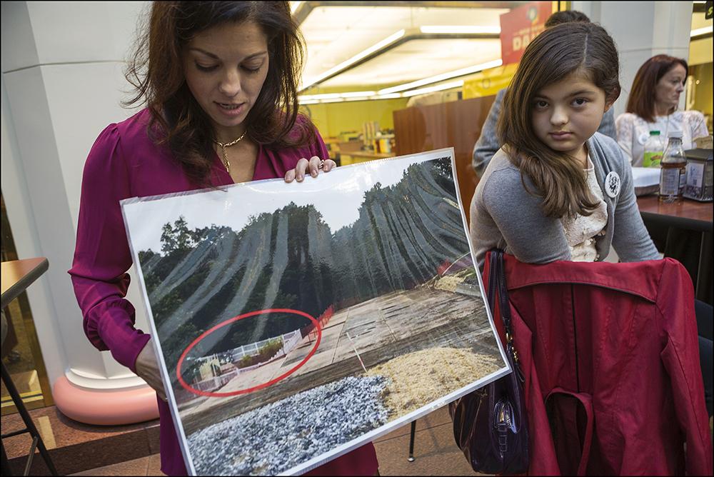 Kvinna visar bild av gasledning bredvid en förskola