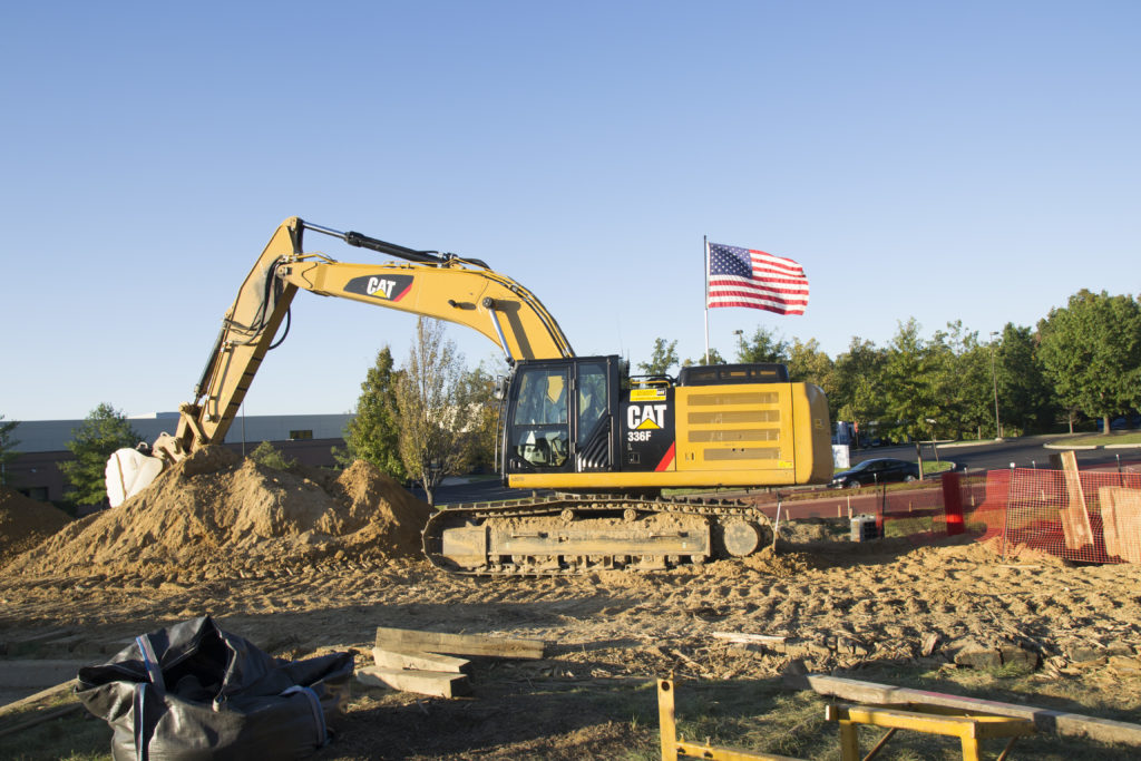 Grävskopa med en vajande amerikansk flagga